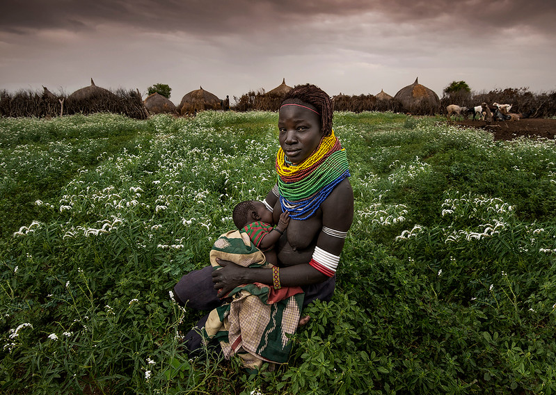 A Nyangatom mother with her baby in front of her village. The neckless she is wearing identifies her as a Nyangatom, originally a Sudanese tribe. This particular neckless is made of plastic. Plastic is now becoming more common as opposed to the more traditional materials like bone or wood.<br /> <br /> Omo Valley, Ethiopia, 2017