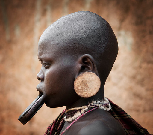 This is Nataere a young women from the Mursi tribe. Women from the Mursi tribe may have their lips cut at the age of 15 or 16.  A small clay plate is then inserted into the lip. Through the years, larger plates are inserted into the lip causing it to stretch.  The larger the clay plate, the more the woman is worth before she gets married.  It is said that the clay plates were originally used to prevent capture by slave traders.  Although very unique and part of their tradition, the Mursi women only wear the plates for a short time because they are so heavy and uncomfortable. It was said that this practice was first carried out to make them look ugly when Arab merchants continually raided their villages in search of slaves. That explanation has been rejected as studies reveal that the plates are a symbol or expression of social status.  Omo Valley, Southern Ethiopia, 2013.