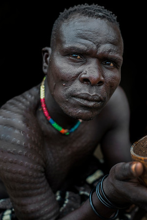 Due to the ongoing conflict in South Sudan many Nyangatom people have escaped into Ethiopia. This nyangatom warrior seen here drinking coffee has found refuge in his families village in the Omo valley.  Omo Valley, Ethiopia, 2017