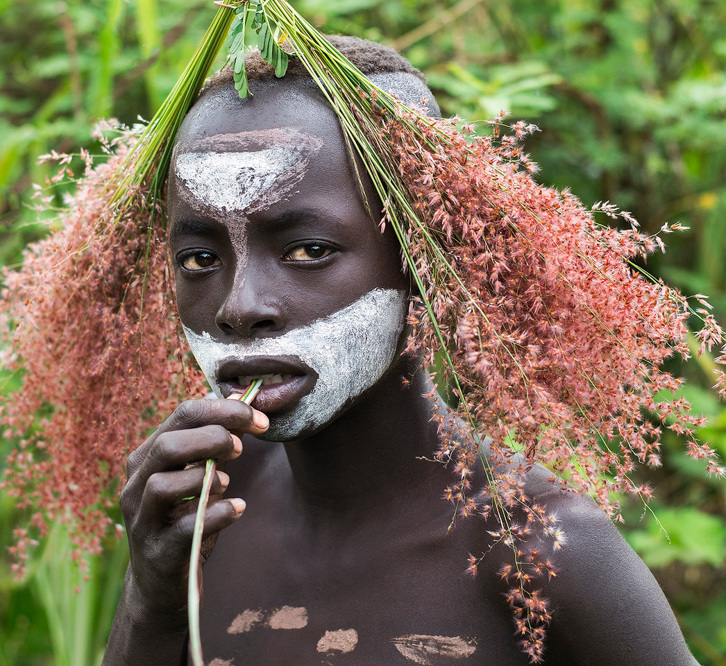 A young Surma man using plants found in the countryside as decoration.<br /> <br /> Southern Ethiopia, 2017
