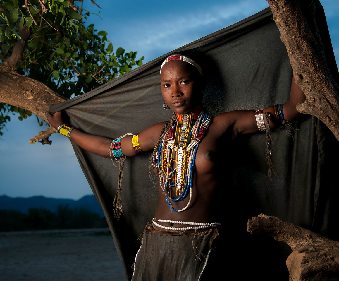 This is Guri, a young virgin from the Arbore tribe.<br /> In the past, the Arbore used to possess the monopoly of the ivory trade. They exchange cattle for agricultural products from the Amare Kokke and acquire worked iron from the Kerre and Borana. The Arbore build their huts slightly oval in shape. The Arbore have a bodily mutilation of raised dots on the chest and abdomen. The Arbore believe in a Supreme Being creator and father of men whom they call Waq.<br /> <br /> Omo Valley, Southern Ethiopia, 2013.