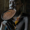 It is uncertain how this bizarre custom of wearing a lip plate came into being. One theory is that lip plating originated as a deliberate disfigurement designed to make women and young girls less attractive to slave traders. Some researchers claim that the size of the lip plate (the bigger the better) was a sign of social importance or wealth within the tribe. Another analysis indicated that the bigger the size of the lip plate, the bigger the dowry a bride would receive on her wedding day. For example, the larger the lip plate, the greater number of cows the bride's father can demand in his daughter's dowry. But some researchers dispute this theory, arguing that marriage of most tribal girls, as well as the size of their dowries, is prearranged long before their lips are cut. Others suggest that lip plating is simply an ornamentation meant to symbolize a woman's strength and self-esteem. The practice is also described as being a sign of social maturity and reaching reproductive age, thus indicating a girl's eligibility to become a wife.<br /> <br /> Suri, South Ethiopia, 2017.