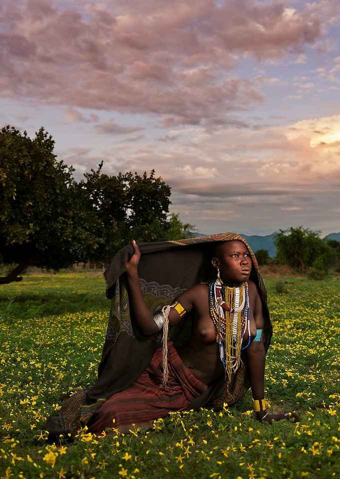 This is Surba, a young woman from the Arbore tribe. The Arbore are agro-pastoral  people  dwelling  in  south-western Omo Valley. Their population is  estimated to be around 7,000. The Arbore territory is a savannah grassland at around 500 meters  elevation. The Weito River flows from north to south and runs into the Lake Chew Bahir, on the border between Ethiopia and Kenya.  The people live  along the lower part of the river.<br /> <br /> Omo Valley, Southern Ethiopia, 2013.