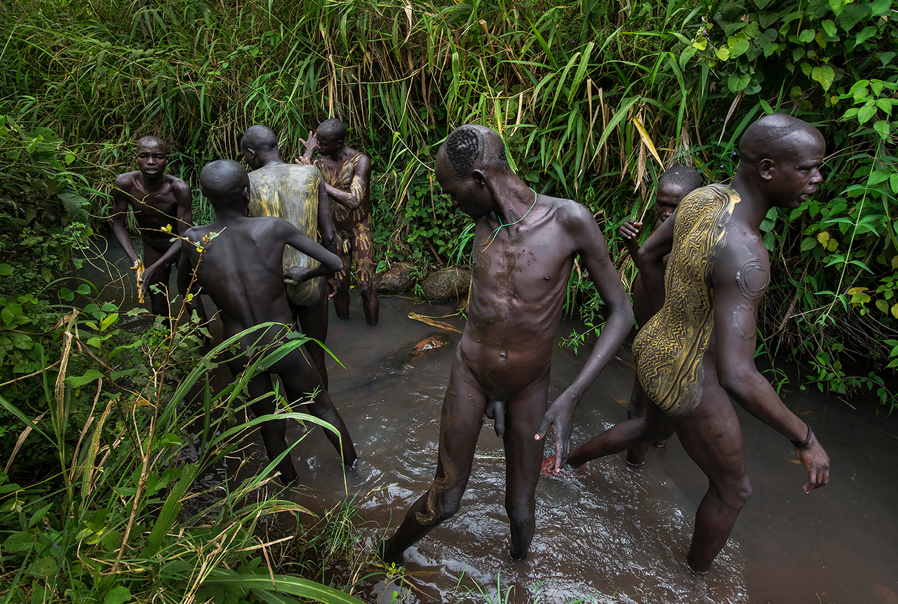 A group of Suri men painting their bodies in preparation for the Donga or Stick fight. The Donga is a very violent tradition were men fight each other with long, solid, wooden stick.<br /> <br /> Suri, Ethiopia, 2017