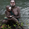 A Suri mother and child sitting by the river. Natural paint obtained from the nearby countryside can be seen on the rocks. They use this paint to make beautiful decorative patterns on their bodies. This has become very popular amongst young children.<br /> <br /> Kibish, Ethiopia, 2017