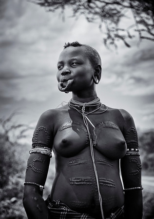Scarring or tribal beatification marks can be used to accentuate the shape of the female body. Mursi women have elaborate symmetrical scarring patterns made on their bodies. They focus on the stomach but also curve around the breasts. The flat skin of the stomach is raised with sharp thorns and then cut.  Omo Valley, Southern Ethiopia, 2013.