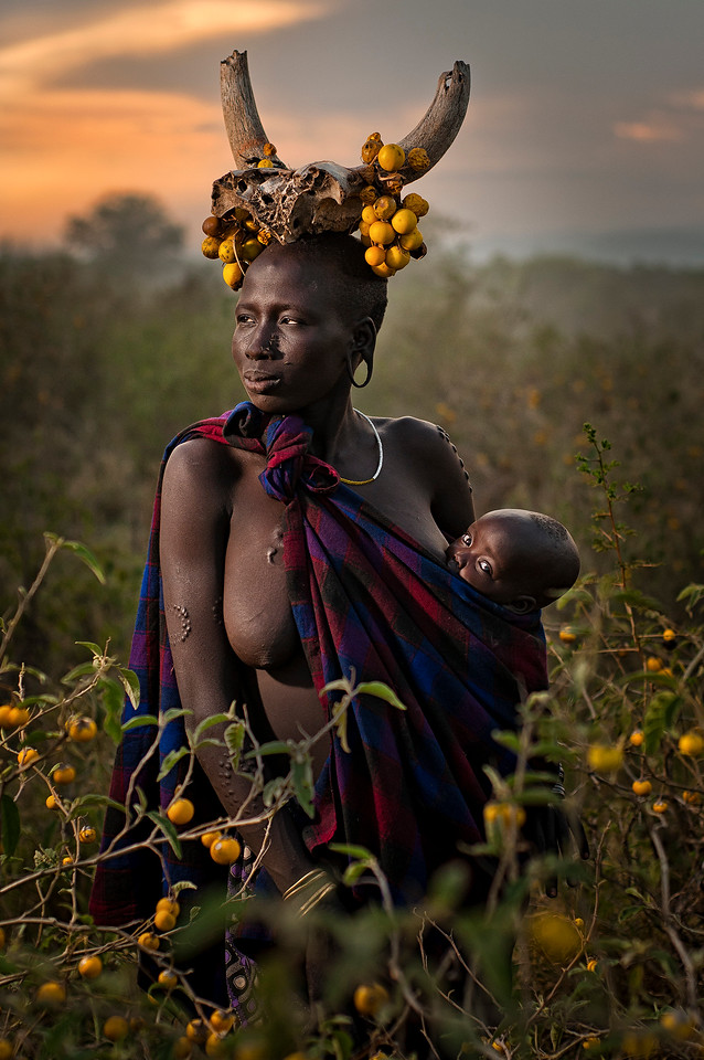 This is Magantu and her baby Bartui. Mursi society has a high level of infant mortality and raising children is greatly valued. Scarring around the hips, on the stomach and breasts can highlight areas associated with fertility. The scars themselves can also remain sensitive for years following their creation and be a source of heightened sensation for those with scars and anyone who touches them.<br /> <br /> Omo Valley, Southern Ethiopia.
