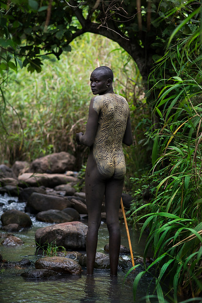 A Suri man painting his body in preparation for the Donga or stick fighting.<br /> <br /> Southern Ethiopia, 2017.