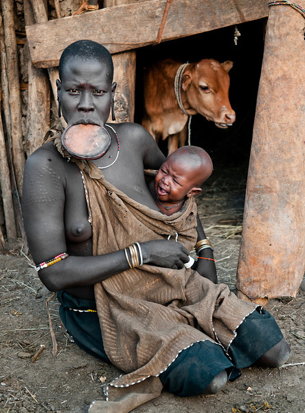 This is Nania and her son koro from the Mursi tribe. There are various rites of passage, educational or disciplinary processes that people undergo. Lip-plates are a well known aspect of the Mursi and Surma, who are probably the last groups in Africa amongst whom it is still the norm for women to wear large pottery or wooden discs or 'plates' in their lower lips.<br /> <br /> Omo Valley, Southern Ethiopia, 2013