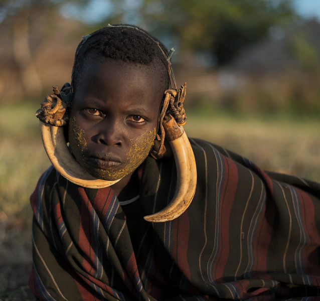 A young Murci girl wearing horns for decoration. <br /> <br /> Omo Valley, Ethiopia, 2017.