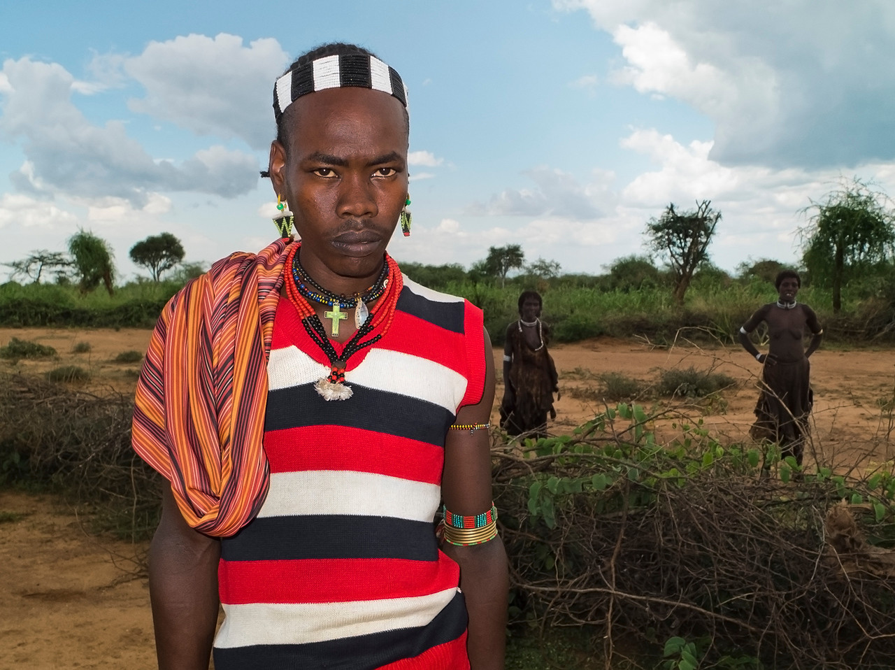 Young man from the Banna tribe with two Hamar women behind. The Banna and Hamar live close together and share many similarities in there customs. <br /> <br /> Omo Valley, Southern Ethiopia, 2013.