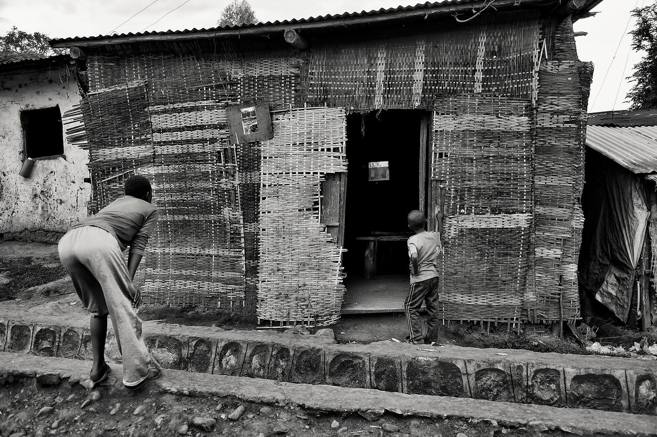 Few families own a television set in the town of Jinka. So many people pay to go into one of these TV huts to view there favourite program, or like these two kids they just try and get a peep from outside.<br /> <br /> Jinka, Southern Ethiopia, 2013.