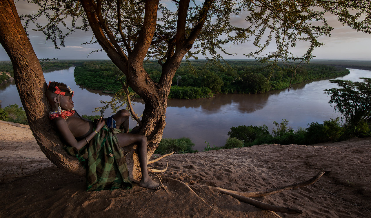 A young Karo girl relaxing whilst enjoying a breathtaking view over the Omo River.<br /> <br /> Omo Valley, Ethiopia, 2017