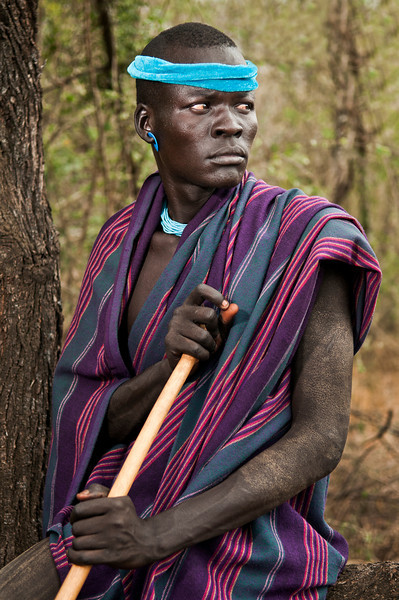This is Olagidain a man from the mursi tribe. Just like any other ethnic tribe in the lower valley, the men must pass a test before they can get married.  A Mursi man is given a stick called a Donga and must face one opponent.  The men then battle it out, beating each other with the sticks. During the fight they protect their most vulnerable parts with coarse cotton cloths. The ceremony takes place every year after the harvests (November- January). All the Surmic groups participate in this ritual as another step up the social ladder for their young men. The fight is symbolic; the adversary has to be defeated without being killed. The victorious young man wins special prestige and, above all, attention from the young, single women. If an adversary is killed, there are serious reprisals for the young man and his family.<br /> <br /> Omo Valley, Southern Ethiopia, 2013.