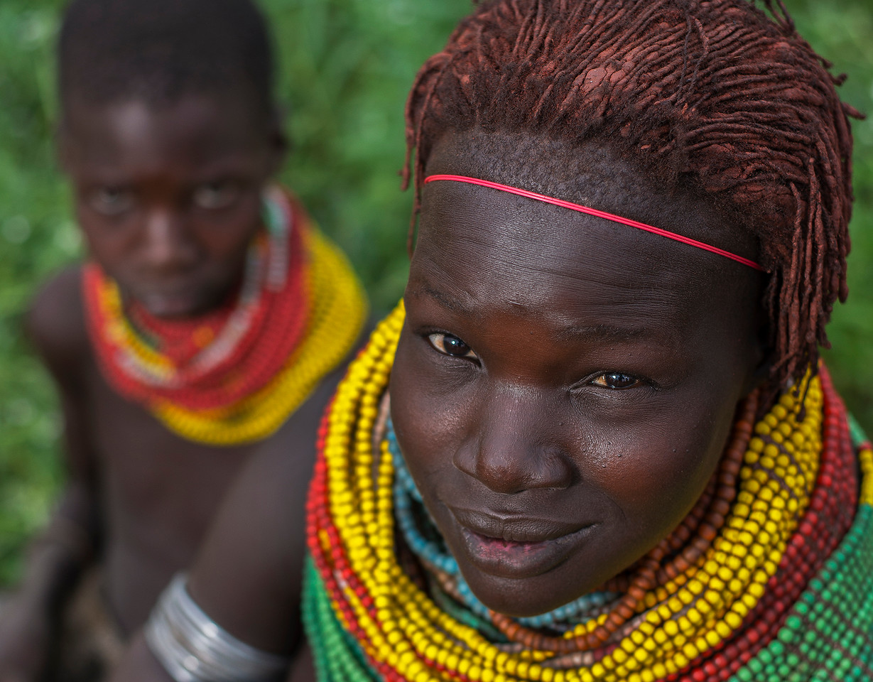 Two members of the Nyangatom tribe. The Nyangatom women wear a traditional, colorful necklace. Although other tribes wear similar ones, none are as big as theirs.<br /> <br /> Omo Valley, Ethiopia, 2017.