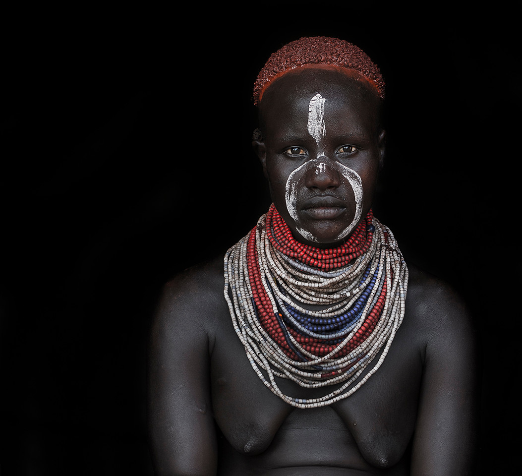 Portrait of a Karo woman. The Karo traditionally paint there faces and wear a colorful necklace although not as large as there rival tribe the Nyangatom.<br /> <br /> Omo Valley, Ethiopia, 2017.
