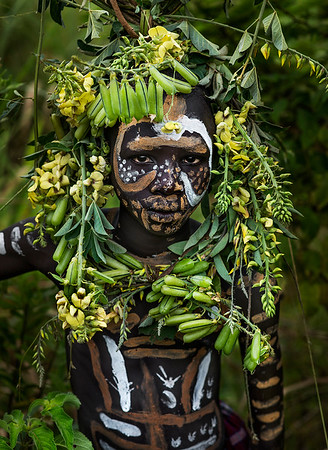 A young Surma man blending into the surrounding vegetation.  Southern Ethiopia, 2017.