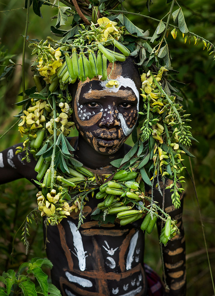 A young Suri man blending into the surrounding vegetation.<br /> <br /> Southern Ethiopia, 2017.