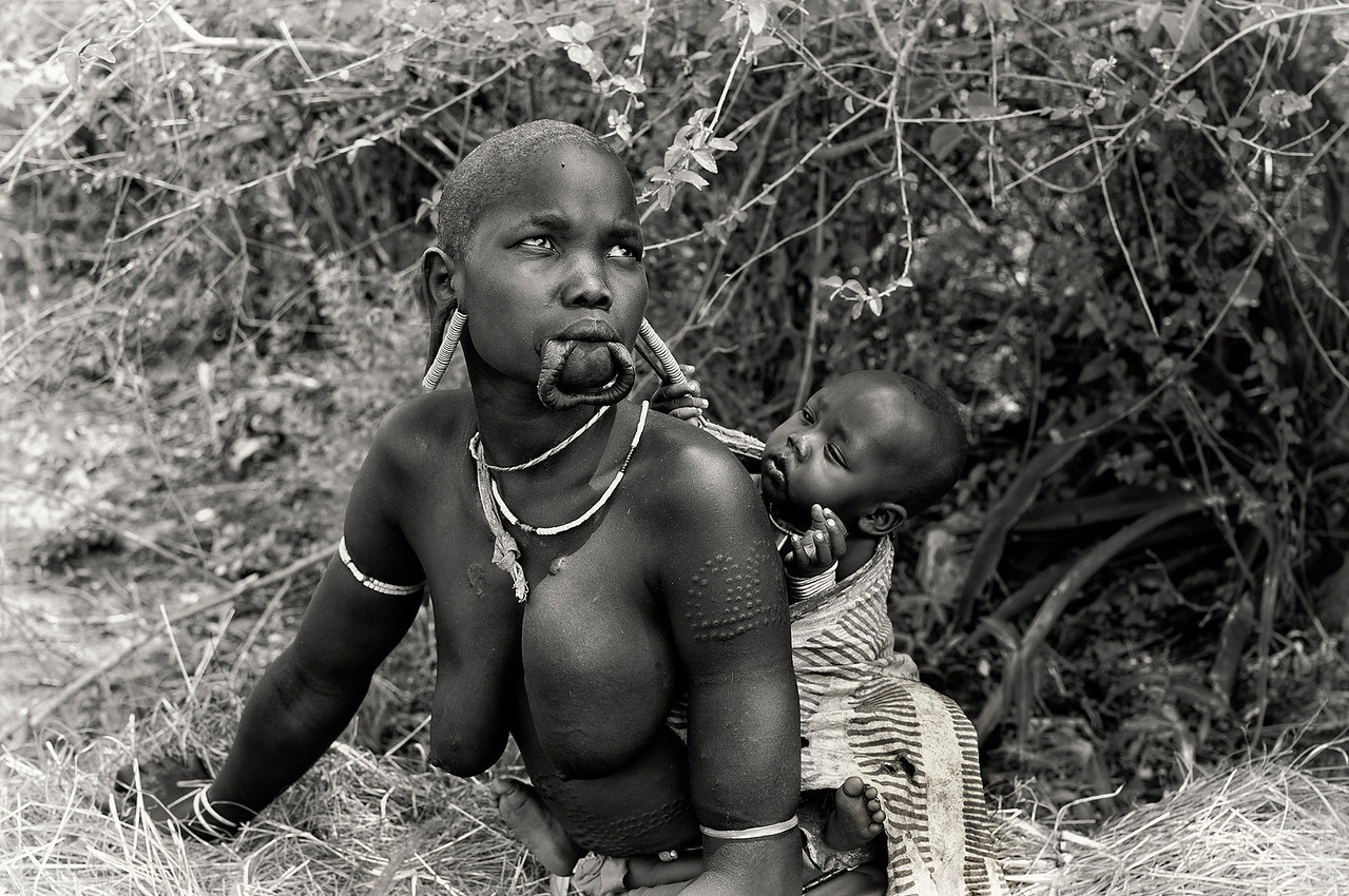 The supposed historical link between lip-plates and the activities of slave traders is an idea that goes back to colonial times. In an article in the September 1938 issue of National Geographic Magazine, C & M Thaw report meeting women with large plates in both their upper and lower lips near Fort Archambault, on the River Chari, about 400 miles south-east of Lake Chad, in what was then French Equatorial Africa.<br /> <br /> Omo Valley, Southern Ethiopia, 2013.