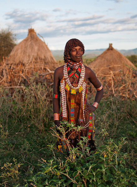 This is Koto, from the Hamer tribe.<br /> There is a division of labour in terms of sex and age. The women and girls grow crops (the staple is sorghum, alongside beans, maize and pumpkins). They're also responsible for collecting water, doing the cooking and looking after the children - who start helping the family by herding the goats from around the age of eight. The young men of the village work the crops, defend the herds or go off raiding for livestock from other tribes, while adult men herd the cattle, plough with oxen and raise beehives in acacia trees.<br /> Sometimes, for a task like raising a new roof or getting the harvest in, a woman will invite her neighbours to join her in a work party in return for beer or a meal of goat, especially slaughtered to feed them.<br /> <br /> Omo Valley, Southern Ethiopia, 2013.
