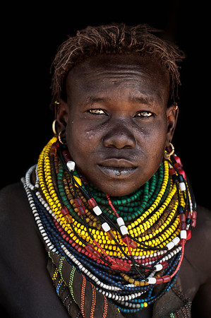 """This is Namailoi, a young woman from the Nyangatom tribe. Other tribes don't like the Nyangatom (mainly because they fear them) and call them pejoratively the Bume, which translates as """"stinking"""". They are indeed fierce warriors which is supposedly demonstrated by their custom to scar their chest; one scar for each killed enemy. Heavy necklaces and long skirts from goat skins, which are richly decorated, are characteristic for the women. Necklaces were traditionally made from dry seeds, but these days they have been largely replaced with colourful glass beads coming from Kenya. The women also decorate themselves with ornamental scarification on their faces, chests, and bellies.  Omo valley, south Ethiopia, 2013."""