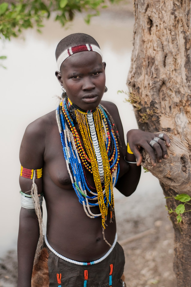 This is Surba, a young woman from the Arbore tribe. Surba  like all young women from her village needs to walk a few kilometers each day to fetch water from a nearby pond. Surba is a virgin as symbolised by her shaved head. Her long colorful necklaces are a very important status Symbol amongst women of all the tribes of the Omo Valley. Each tribe has there own distinct color, length and materials used.<br /> <br /> Omo Valley, Southern Ethiopia, 2013.
