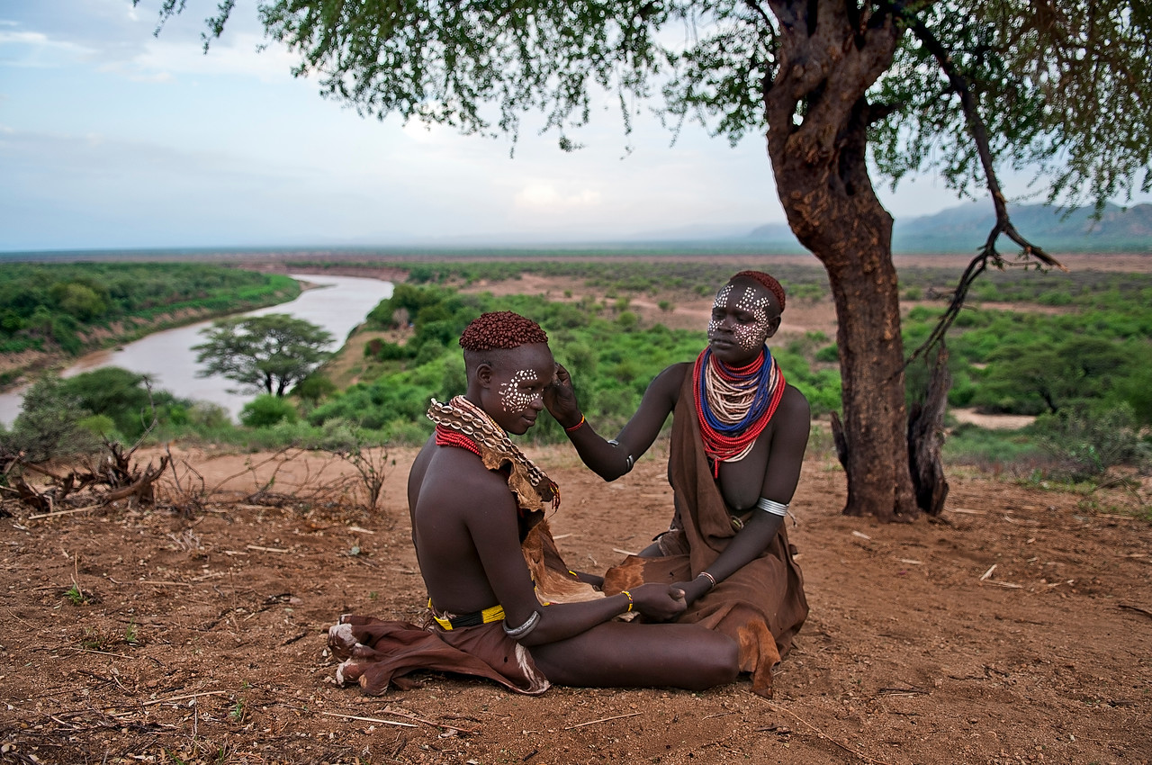 These are borza and Magi, two friends from the Karo tribe. The most striking thing about Karo people's symbolic and ornamental expressions is the painted body and face decorations.            <br /> This is an elaborate process, which ranges from fine and elaborate details to rough, but striking paintings traced with the palms or fingers. The most beautiful expression is in the facial and chest paintings that combine white (chalk), black (charcoal), yellow, ochre, and red earth. They often imitate the spotted plumage of a guinea fowl.<br /> <br /> Omo valley, south Ethiopia, 2013.