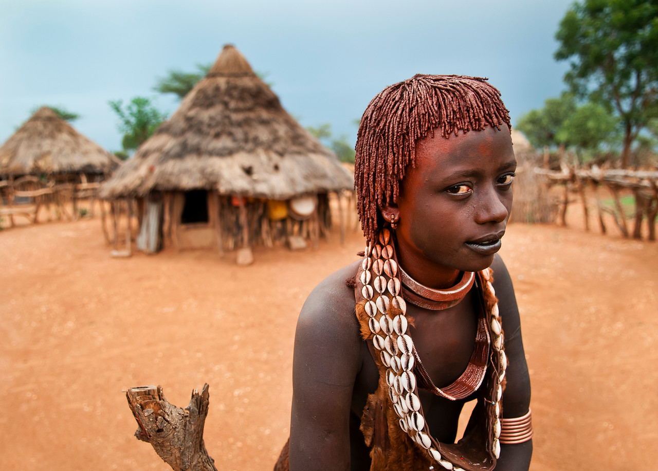 This hamar woman is a second wife, this is symbolised by her two metal necklaces. The Hamar women who are not first wives have a really hard life, being more of a slave than a wife. Hamer women cover there body and hair with clay, butter and animal fat, and the more scars one has on her back, the higher her status.<br /> <br /> Omo Valley, Southern Ethiopia, 2013.