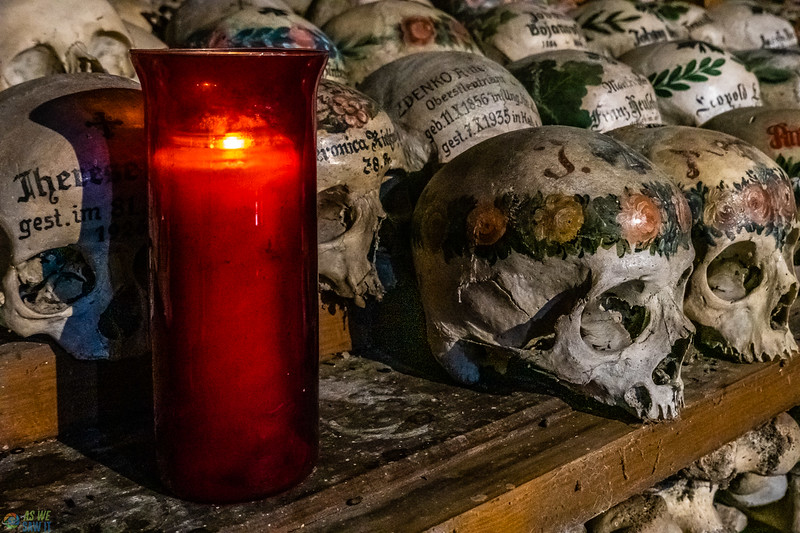 Decorated skulls inside the bone house with a candle lit in remembrance.