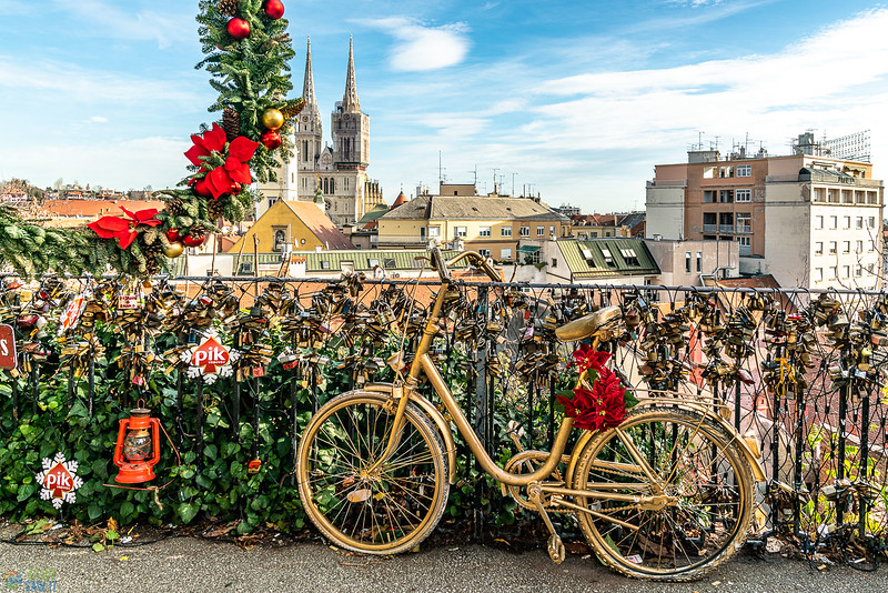 Beautiful view from castle at christmas with a gold painted bicycle in the fore ground and the city of zagreb behind.