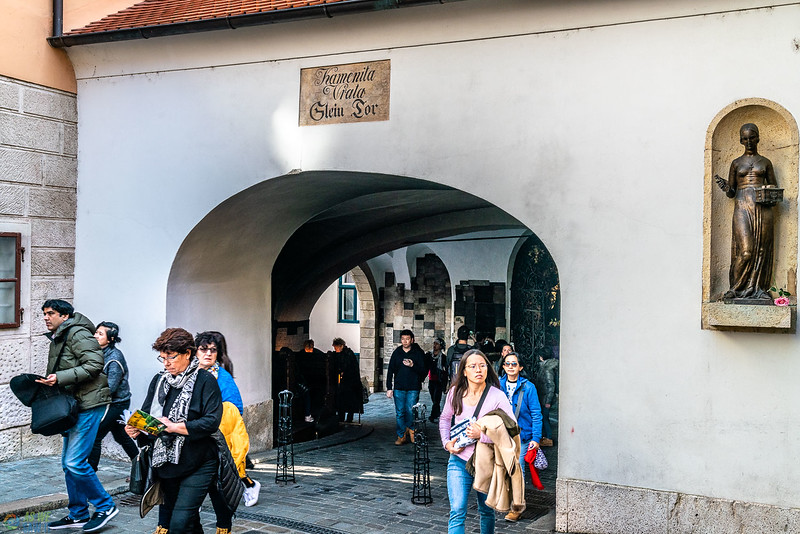 Tourists existing the arch of stone gate in zagreb.