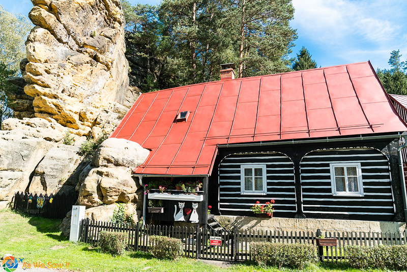 House with wood siding and red roof, built into a rock in Jetrichovice, Czech Repubic.