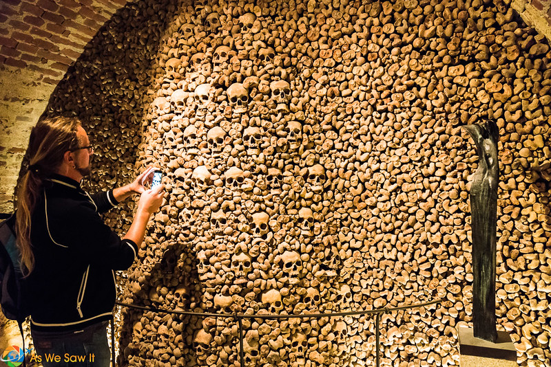 Woman takes photo of a wall of human skulls and bones at the ossuary in Brno.