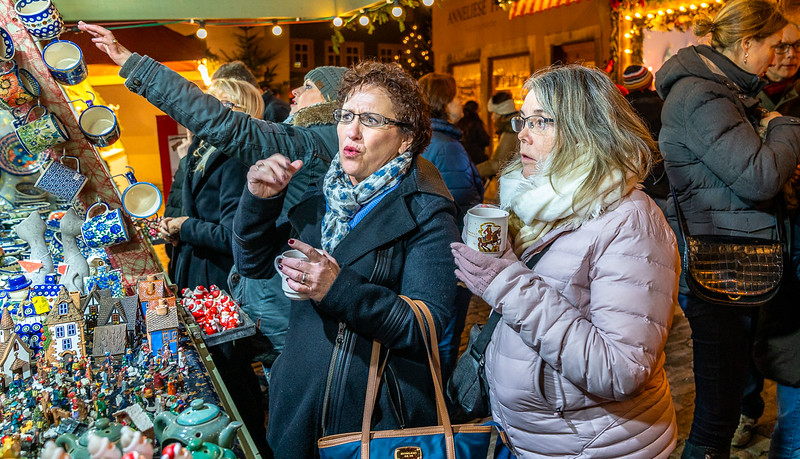 Two women hold mugs of hot gluhwein at one of the European Christmas markets.