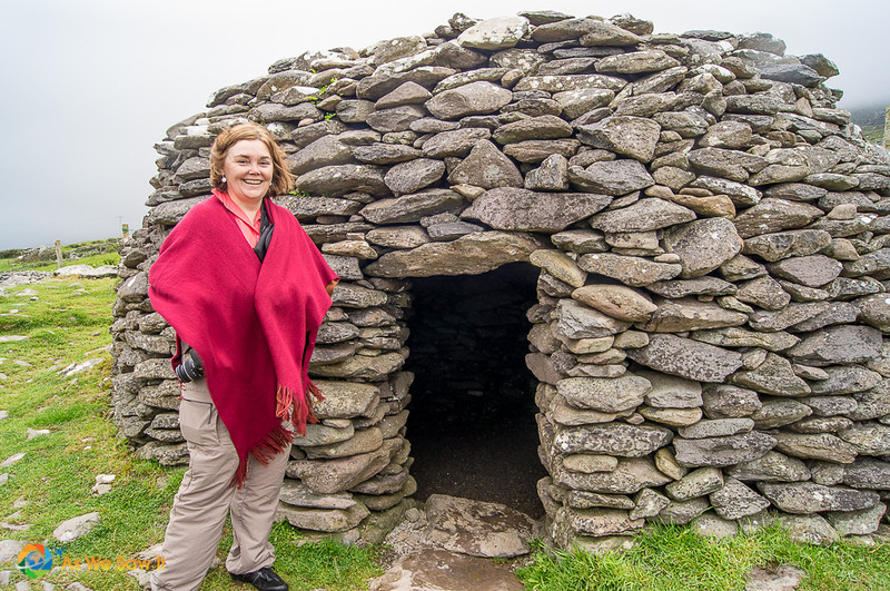 Linda stands in front of a Fahan rock beehive hut on Dingle Peninsula.