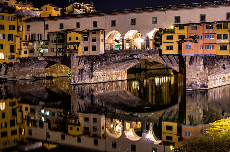 The Ponte Vecchio reflected in the still waters of the nght Arno River.