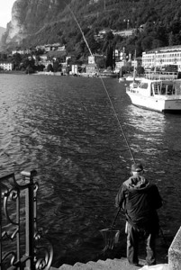 A man catching a fish in the early morning in Menaggio.