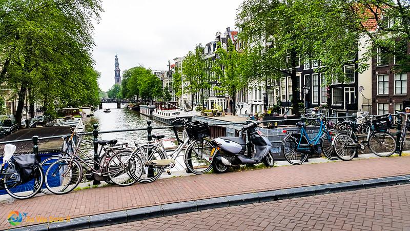 Vélos sur pont sur un canal, maisons hollandaises et Westerkerk en arrière-plan.