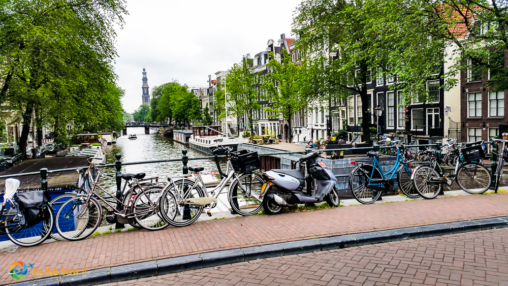 Bicycles on bridge over a canal, Dutch houses and Westerkerk in background.