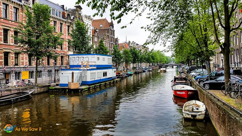 Maisons hollandaises typiques sur canal, avec péniche et petits bateaux à moteur sur l'eau