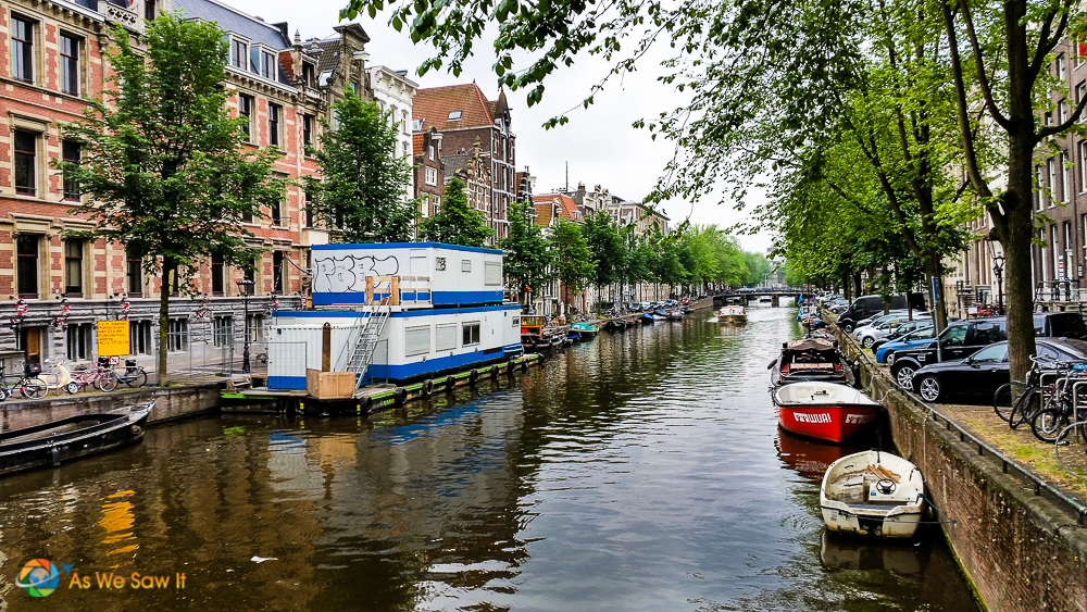 typical Dutch houses on canal, with houseboat and small motorboats on the water