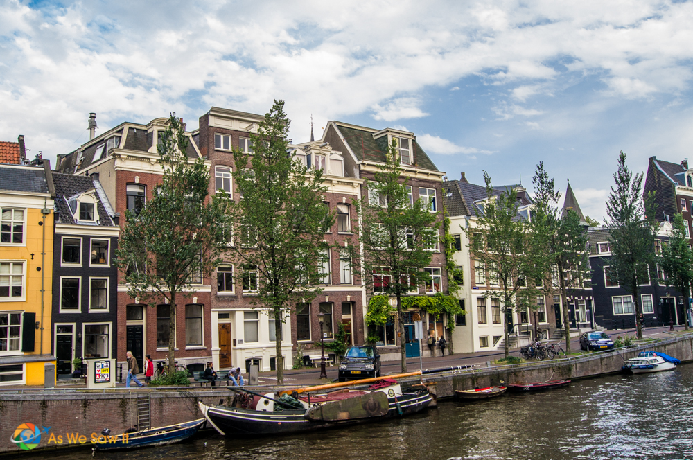 Houseboats line the bank in Amsterdam, and classic Dutch style architecture in the background.