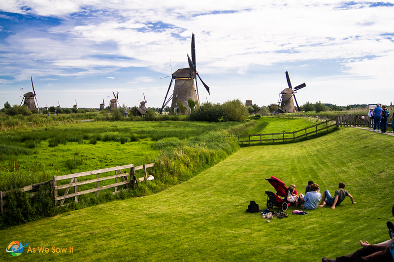 A group of tourists sit on the grass looking at the Kinderdijk Netherlands windmills in background.