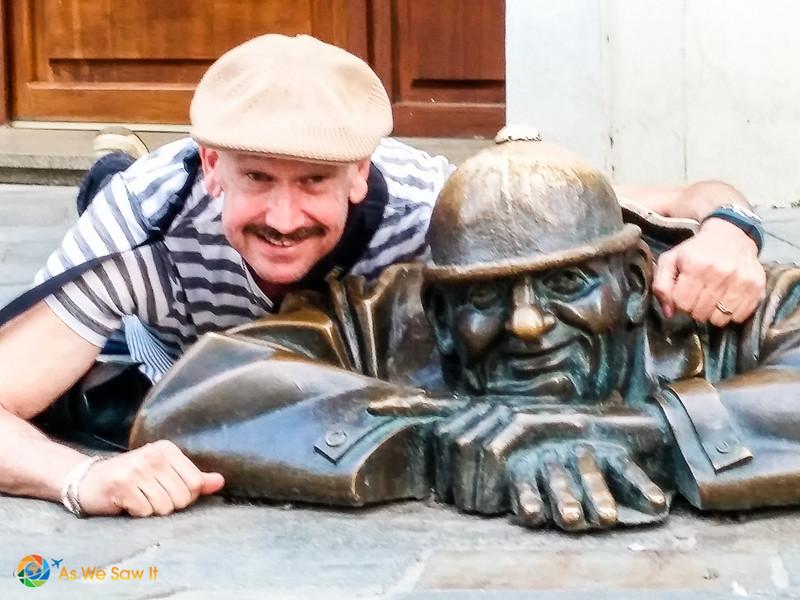 Man posing with a bronze statue in Bratislava, Slovakia.