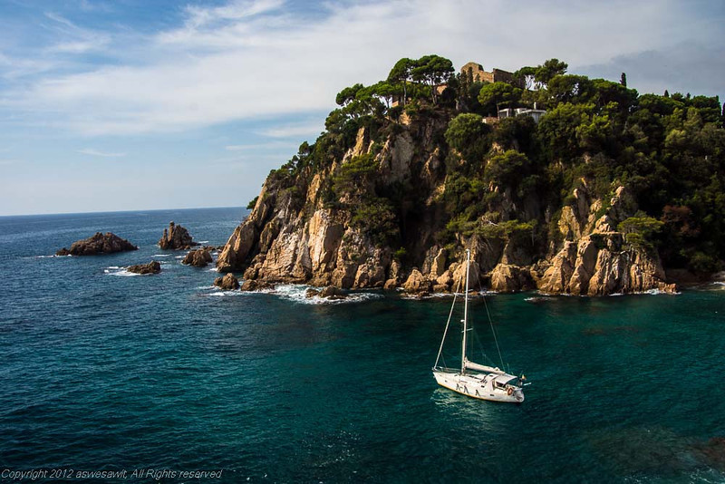 White sailboat amid luminous blue Mediterranean water, in front of cliffs.