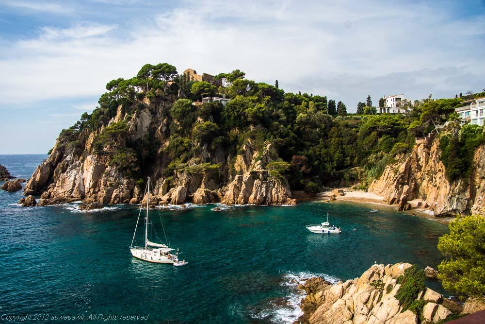 Two white pleasure boats afloat along the rocky Costa Brava coastline, Spain