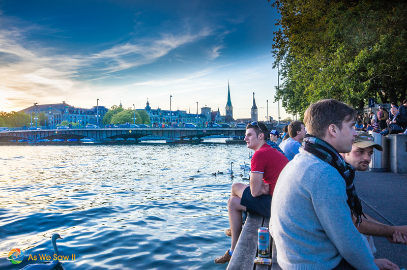 People sitting along River Limmat. Bridge and city in background.