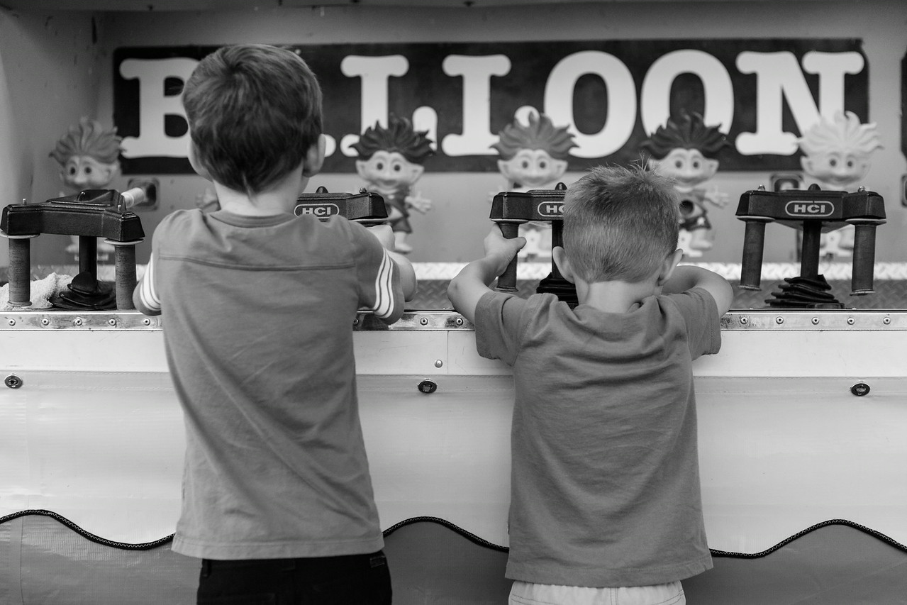 B&W conversion of them playing a game at the fair. Digital. Summer 2014.
