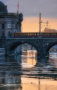 Water with ice floes reflects evening sky while S-Bahn train crosses bridge at Museum Island