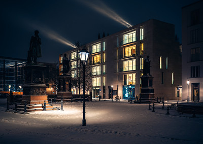 Snow covered Schinkel Place with lightbeams pointing towards Berlin palace